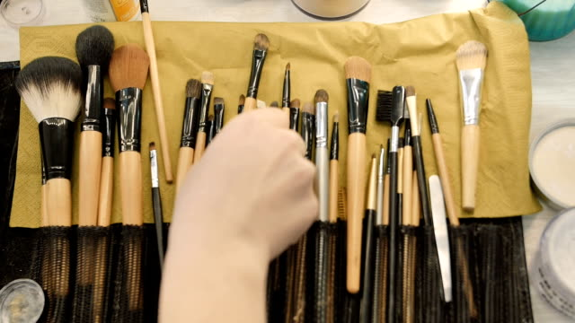 Make-up artist taking brushes from professional brush set. Beauty, makeup and fashion concept video