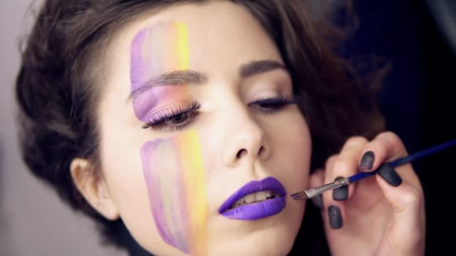 Makeup artist uses brush to apply lipstick to model's lips. Model with false lashes and face art painting preparing to the fashion show. Slowmotion shot. video