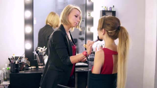Make-up artist using big brush to apply face powder and finishing make up for a young blonde woman in red dress. Beauty saloon. Slowmotion shot video