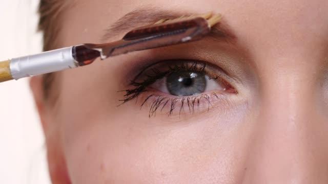 makeup artist using eyebrow brush - wschodnio europejski filmów i materiałów b-roll