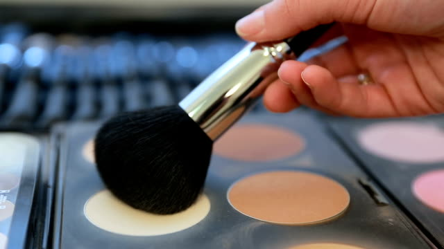 Makeup artist using powder brush to take a color from the makeup palette... video