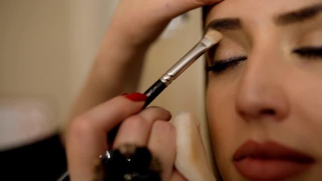 stockvideo's en b-roll-footage met make-up artist werken aan haar vriend. echte mensen. - oogschaduw