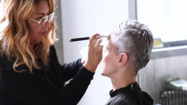 makeup artist working on female model with short grey hair - kosmetyczka praca w salonie piękności filmów i materiałów b-roll