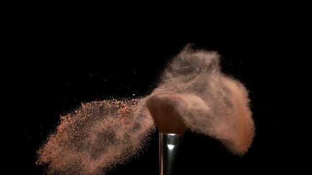vidéos et rushes de pinceau de maquillage répandre la poudre de fard à joues sur fond noir, slow motion 4k - pinceau à maquillage