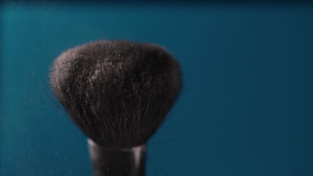 Make-up brush with powder close up on blue background. Make-up brush with powder close up on blue background. Cosmetics, tools, powder, haze foundation make up stock videos & royalty-free footage