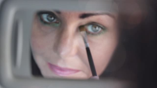 Makeup in a car Close up, rear view of a woman putting on make-up in a car. Putting on some eye shadows, looking at passenger's mirror donna stock videos & royalty-free footage
