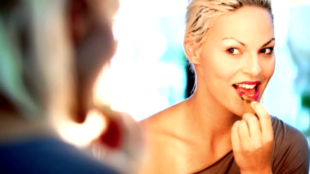 Makeup. Closeup of adult blond woman applying makeup on her face. She's in front of big mirror putting on some pink lipstick. She's smiling. Shot from behind, mirror reflection is in focus. lip balm stock videos & royalty-free footage