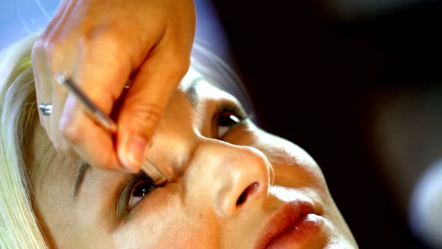 Makeup. Closeup of adult blond woman at makeup and cosmetics salon. She's in front of big mirror and beautician is applying face powder onto her skin She's smiling. Top view. lip balm stock videos & royalty-free footage