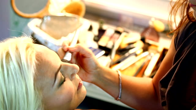 Makeup. Closeup of adult blond woman at makeup and cosmetics salon. She's in front of big mirror and beautician is applying face powder and eyeshadow onto her skin She's smiling. Top view. lip balm stock videos & royalty-free footage