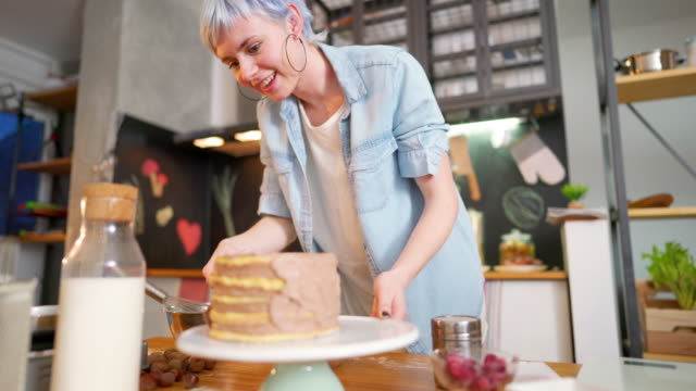 Making a cake with love Young woman making a cake at her kitchen. blue hair stock videos & royalty-free footage