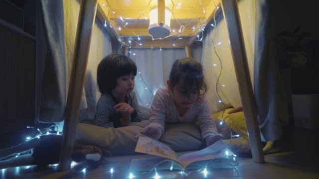 Making a camp at home during quarantine Little girl and boy reading a book in fort made out of pillows and cushions in living room fort stock videos & royalty-free footage
