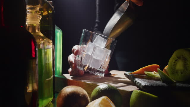 Making a cocktail with fresh kiwi fruit, lime and orange video