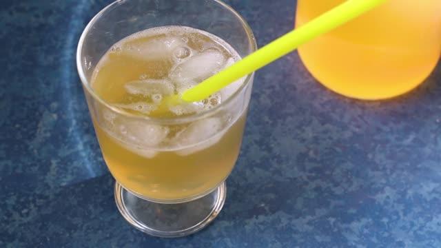 vidéos et rushes de faire un thé fermenté maison froid et sain avec des propriétés probiotiques naturelles. boire avec de la glace dans un bol en verre sur un fond bleu. - infusion pamplemousse