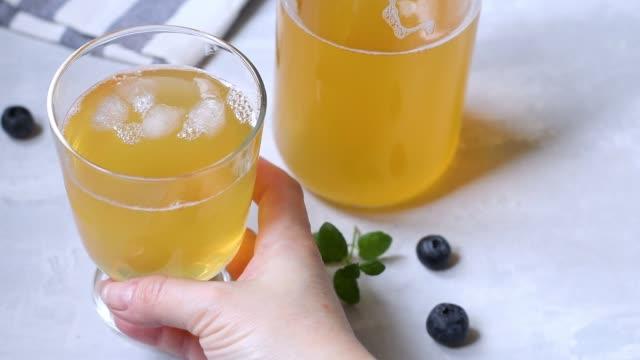vidéos et rushes de faire un thé fermenté maison froid et sain avec des propriétés probiotiques naturelles. buvez avec de la glace dans un bol en verre sur un fond léger. - infusion pamplemousse