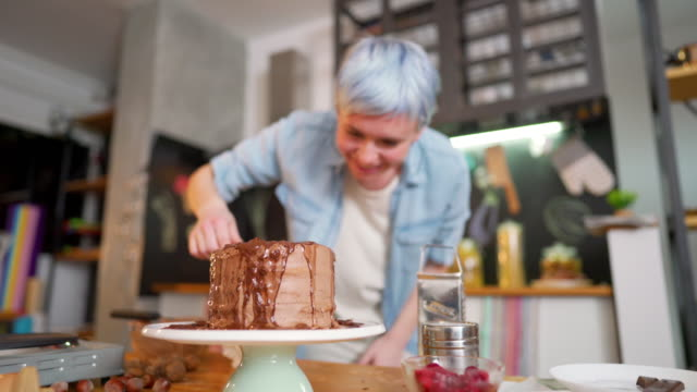 Making a delicious chocolate cake Young woman making a cake at her kitchen. blue hair stock videos & royalty-free footage
