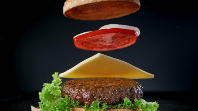 fare un hamburger con patty di manzo alla brace che cade, formaggio cheddar, panino al sesamo e verdure al rallentatore - hamburger video stock e b–roll
