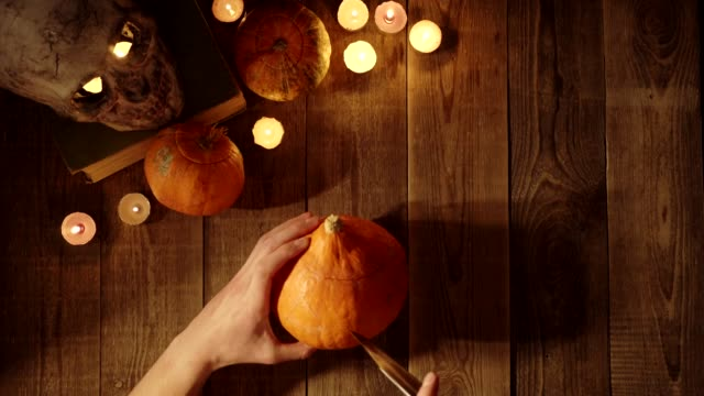 making a lantern on halloween from a pumpkin cutting out eyes with a knife - zucca legenaria video stock e b–roll