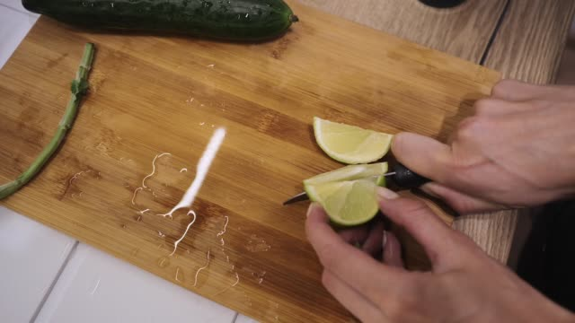 making a mojito cocktail, slicing a lime with a knife on a wooden board