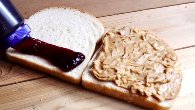 vídeos de stock e filmes b-roll de making a peanut butter and jelly sandwich - jam jar
