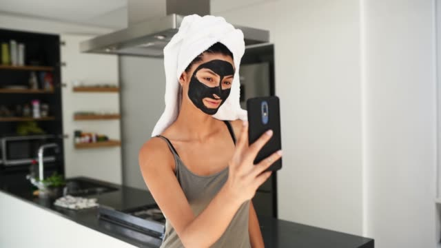 Making a selfie. Young Latin woman is having a spa day at home. She is text messagiing on mobile phone body care stock videos & royalty-free footage