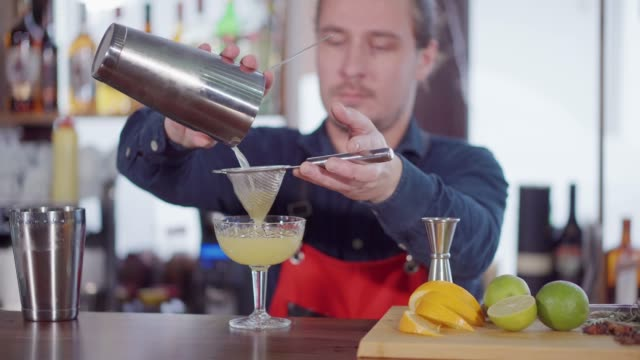 Making a simple cocktail at bar counter. Portrait of a professional bartender sieving cocktail in a glass at bar counter. Making a refreshment to client. margarita stock videos & royalty-free footage