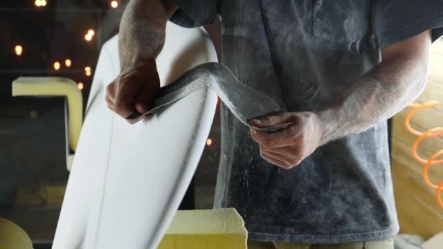 stockvideo's en b-roll-footage met shaper maakt een surfplank en beschuurt de surfplank met een schuurgereedschap. - sportartikelen
