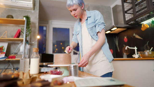 Making a sweet surprise for someone Young woman making a cake at her kitchen. blue hair stock videos & royalty-free footage