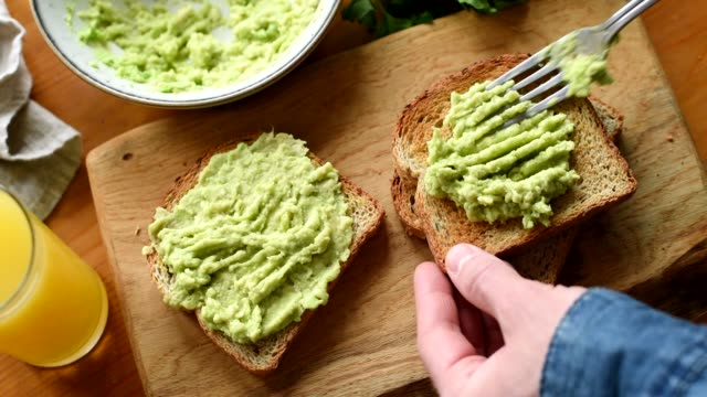 Making avocado toast HD footage Making avocado toast. Man spread avocado on toasted sandwich bread. Cooking food process. Top view avocado stock videos & royalty-free footage