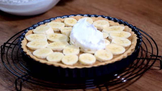 Making banana cream tart with whipped cream.
