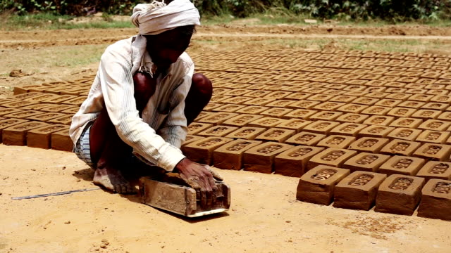 Making bricks Manual worker making bricks using wet soil outdoor during summer season. brick stock videos & royalty-free footage