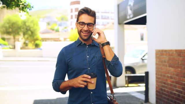 making calls during his morning coffee run - trentenne video stock e b–roll