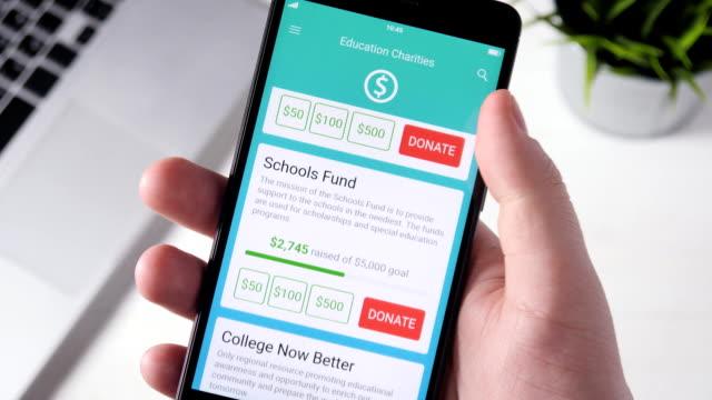 att göra välgörenhet donation till pedagogisk organisation med smartphone-appen - välgörenhet bildbanksvideor och videomaterial från bakom kulisserna