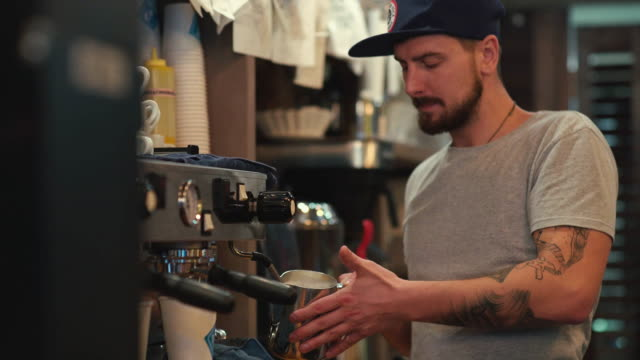 コーヒーを作る。バリスタは、牛乳を加熱します。ミルクの泡 ビデオ