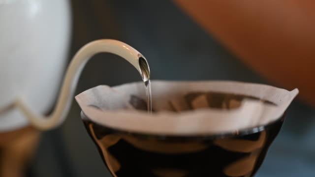 herstellung von kaffee tropfen hand tropf kaffee gießen heißes wasser auf kaffeeboden home brauen hipster lebensstil - koffeinmolekül stock-videos und b-roll-filmmaterial