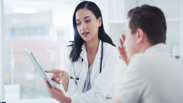 Making consultations as simple as one, two, tap 4k video footage of a young doctor using a digital tablet with her patient during a consultation test results stock videos & royalty-free footage