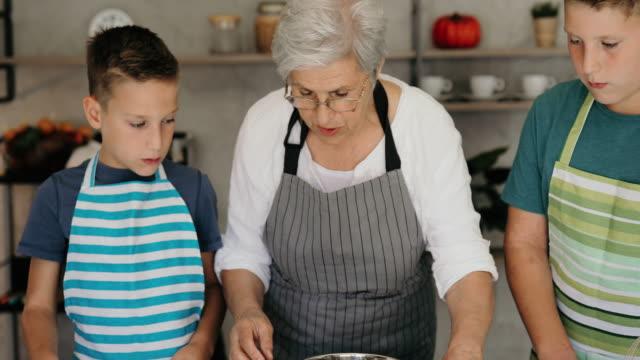 making cookies with grandma is always a great fun - внук стоковые видео и кадры b-roll
