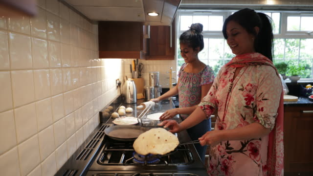 Making Dinner Preparations A side-view shot of a mother and daughter cooking Chapatis in the kitchen. indian family stock videos & royalty-free footage
