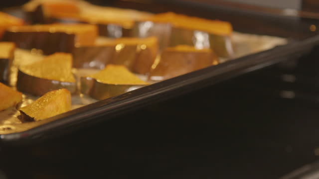 Making filling for homemade pumpkin pie. Roasting fresh pumpkin pieces in oven video