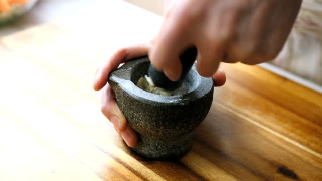 making garlic paste using mortar and pestle