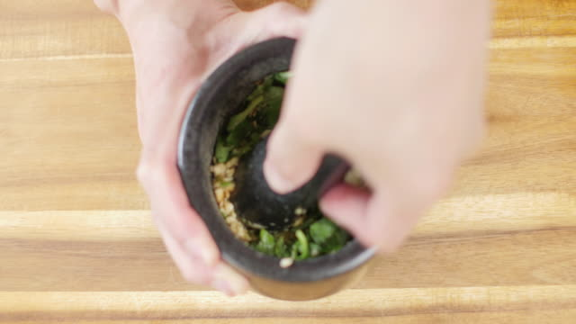 making green pesto sauce top view of close up shoot making green pesto sauce by using Mortar and pestle pine nut stock videos & royalty-free footage