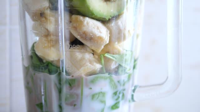 stockvideo's en b-roll-footage met groene smoothie maken in een blender. gezond eten. - milkshake