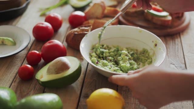 Making guacamole - crushing avocado, steadicam close-up
