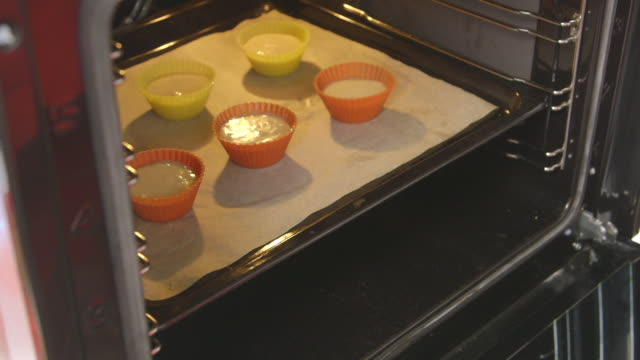Making homemade muffins in brightly coloured rubber cups baked in the oven video