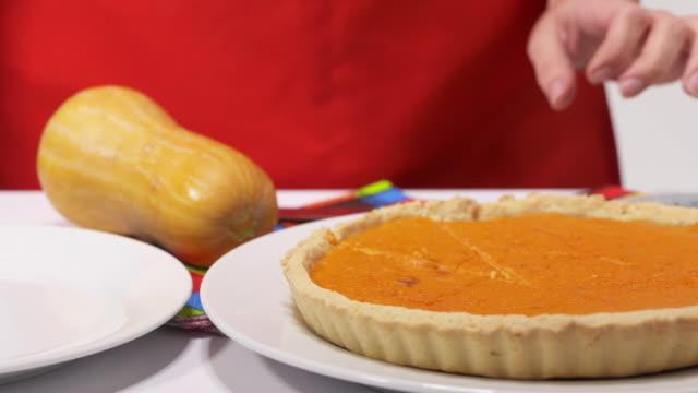 製作與新鮮的南瓜泥自製南瓜餅。女人削減一塊餡餅 - pumpkin pie 個影片檔及 b 捲影像