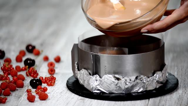 vídeos y material grabado en eventos de stock de hacer tarta casera de tres mousse de chocolate. verter la mousse de chocolate en la forma. - suflé