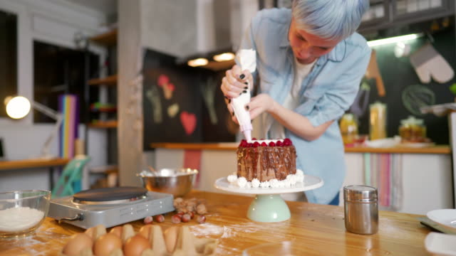 Making magic with cream Young woman making a cake at her kitchen. blue hair stock videos & royalty-free footage