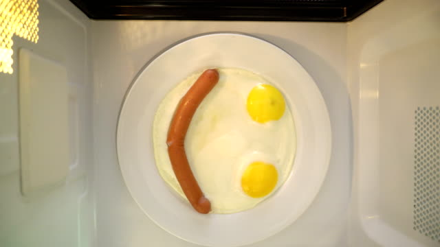 Making microwave breakfast meal. Smiling face of fried eggs and sausage
