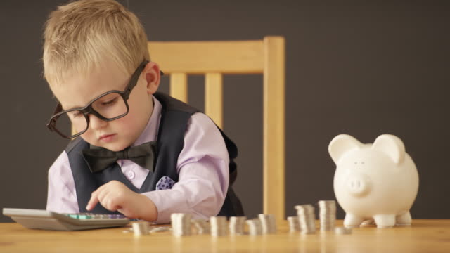 Making Money in the Business Cute toddler dressed up in business clothing counts money using a calculator and smiling in front of a blackboard background. piggy bank stock videos & royalty-free footage