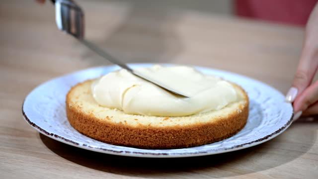 Making of Boston Cream Pie. Hand putting cream on freshly baked cake video