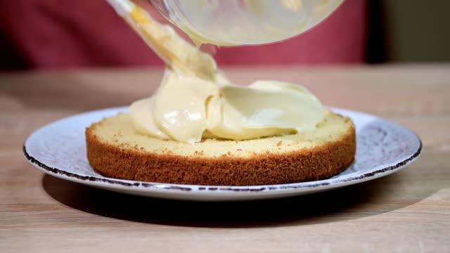 boston kremalı pasta yapımında. taze pişmiş kek üzerine krema koyarak el - muhallebi stok videoları ve detay görüntü çekimi